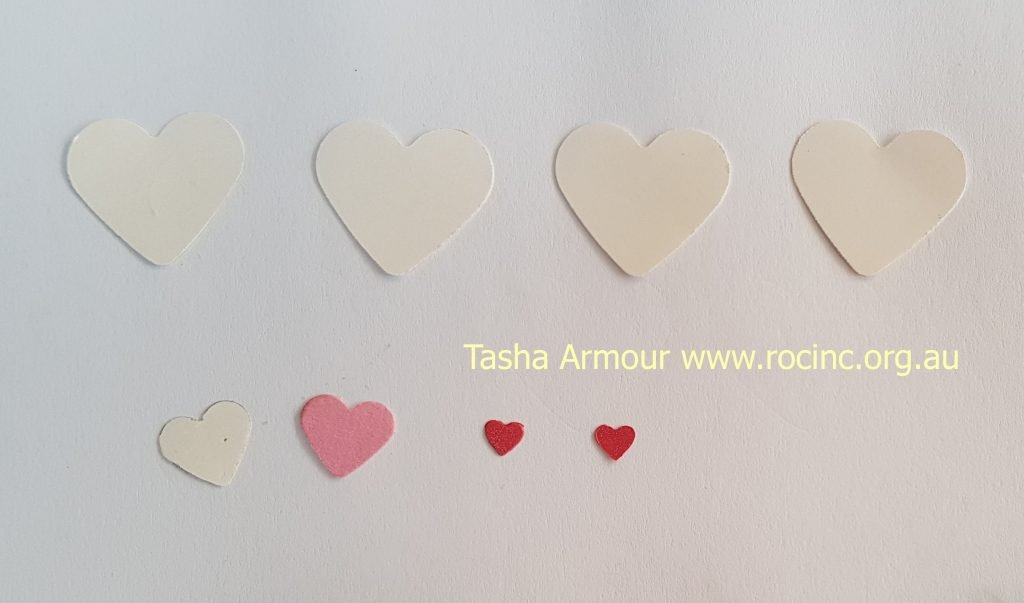 you will need to cut out 4 large white hearts, 1 medium white heart and 1 medium pink heart, 2 small red hearts.